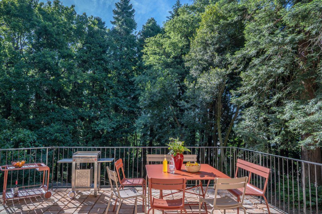 Terrasse du gite sur les arbres centenaires, mobilier Fermob et plancha