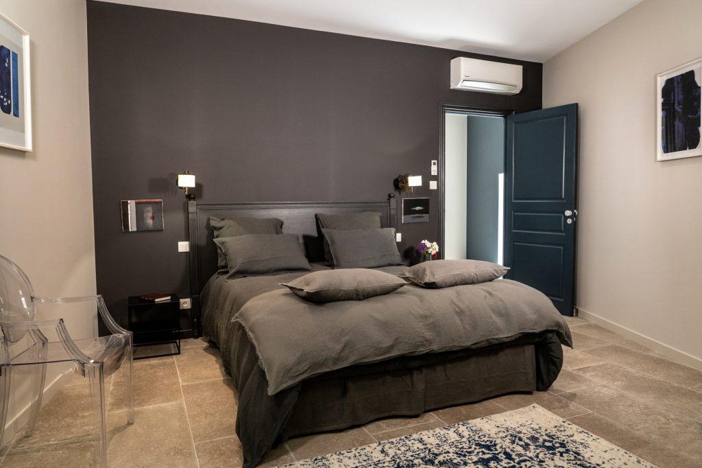 La chambre charbon et son grand lit deux places, au design soigné.